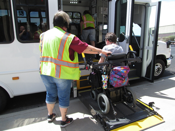 Wheelchair Accessible Bus with driver assisting person in a wheelchair onto lift